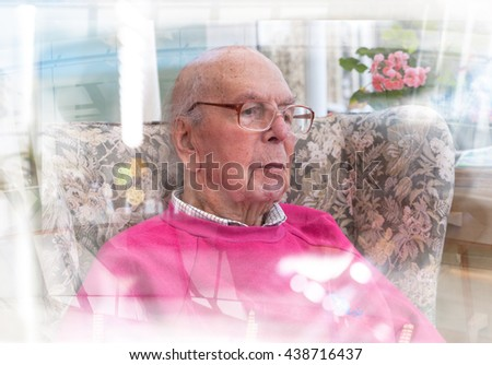 Portrait of 95 years old English man sitting in chair in domestic environment with glass reflection effect. Health and care concept - stock photo