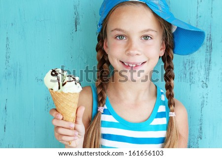 Portrait of 7 years old kid girl eating tasty ice cream over blue - stock photo