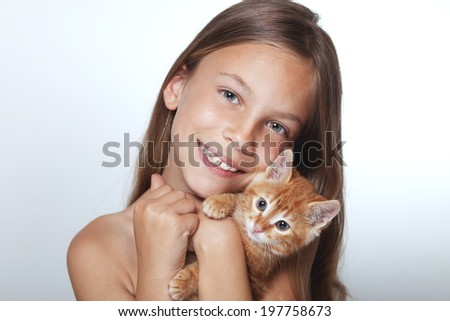 Portrait of 7 years old kid girl holding small kitten - stock photo
