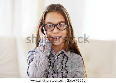 Portrait of 8 years old school girl wearing glasses calling by mobile phone - stock photo