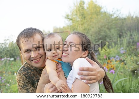 Portrait of Young adult and happy family get stroll on the green summer garden and sky background Baby between parents - stock photo