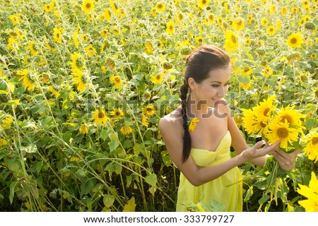 portrait of young adult beautiful joyful latin hispanic woman with long brunette hair wearing yellow dress in sunflower field girl inhales aroma of wild flowers Copy space for inscription - stock photo