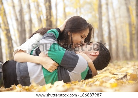portrait of young adult Beautiful latin hispanic couple lying on fresh yellow autumn leaves kissing and hugging Cute pair people looking at each other on fall trees in ?ity park background  - stock photo