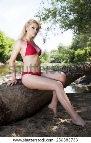 Portrait of young adult beautiful sensuality sexy and attractive pretty blonde babe woman in red bikini posing on a beach - stock photo