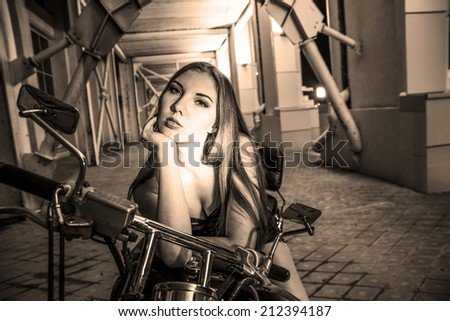 Portrait of young adult caucasian Biker girl in black shorts on a motorcycle Cute sexy woman with long white hair looking at camera Empty copy space for inscription - stock photo