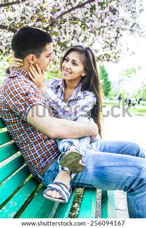 Portrait of Young adult couple sitting together embrace on spring park green wooden bench under cherry or apple tree blossoms Man and woman Romantic date in city town central summer park - stock photo