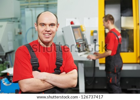 Portrait of young adult experienced industrial worker over industry machinery production line manufacturing workshop - stock photo