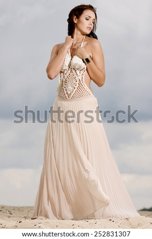 Portrait of young adult fashionable pretty sexy and sensuality attractive beauty brunette woman in white dress on the sand and background blue cloud sky - stock photo