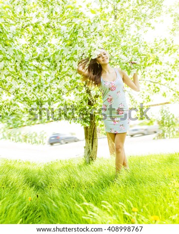Portrait of young adult laugh caucasian Girl holding branch with blooming spring flowers on apple tree background. Full length Cute female standing barefoot on fresh green grass - stock photo