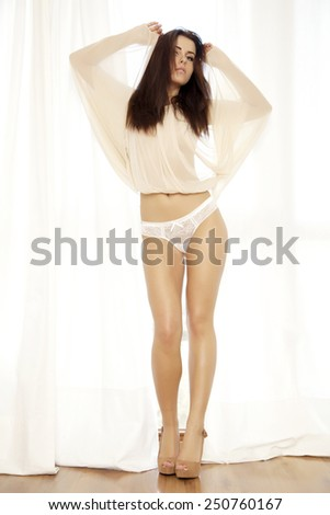 Portrait of young adult slim sexy and attractive sensuality brunette woman in brown blouse and white panties lingerie against the sunny window in luxury style apartment - stock photo