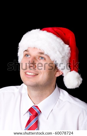 portrait of young adult with santa cap, looking up, studio shoot isolated on black background - stock photo