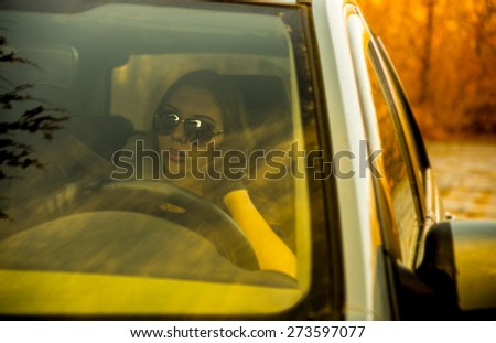 Portrait of young adult Woman in stylish unisex sunglasses and leather gloves looking through the car side window glass with long brown hair on orange or yellow autumn park with trees background - stock photo