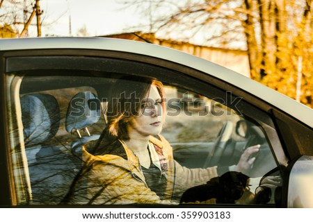Portrait of young adult Woman in stylish unisex yellow jacket looking through the car side window glass with brown hair on orange or yellow autumn park with trees background - stock photo