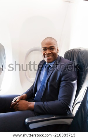 portrait of young african american businessman on airplane - stock photo