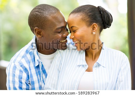 portrait of young african american couple looking at each other outdoors - stock photo