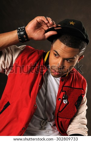 Portrait of young African American hip hop man over dark background - stock photo