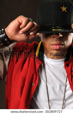 Portrait of young African American man putting on baseball hat over dark background - stock photo