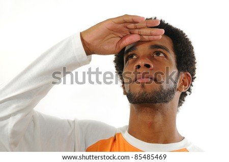 Portrait of young african american man with hand ever the eyes and looking up isolated - stock photo