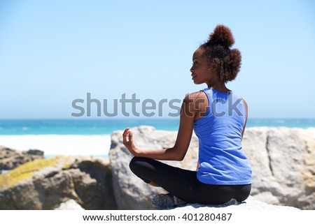 Portrait of young african american woman sitting a rock at beach in yoga pose - stock photo
