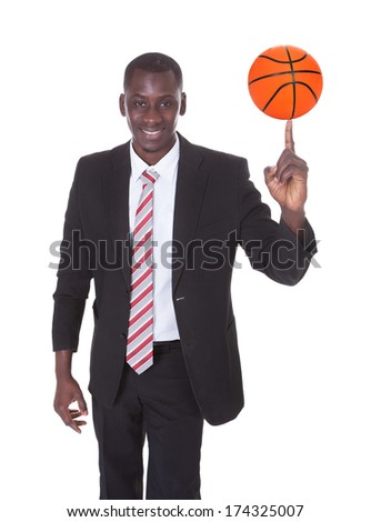 Portrait Of Young African Businessman Spinning Basketball - stock photo