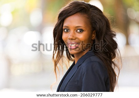 portrait of young african businesswoman standing outdoors - stock photo