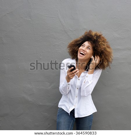 Portrait of young african female laughing with earphones and cell phone - stock photo