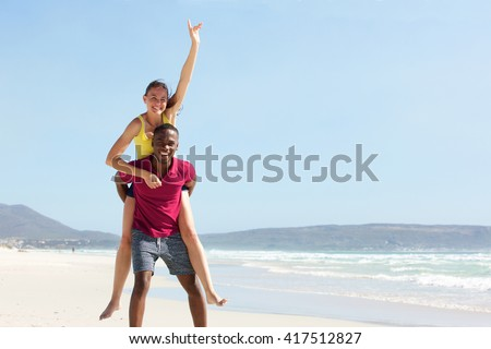 Portrait of young african man carrying girlfriend on his back at the beach - stock photo