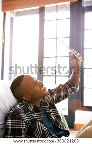 Portrait of young african man sitting at home and taking selfie with a digital tablet - stock photo