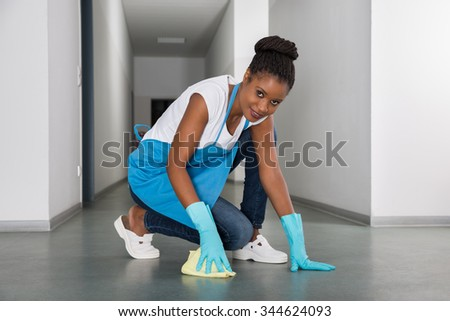 Portrait Of Young African Woman Cleaning Floor With Cloth - stock photo