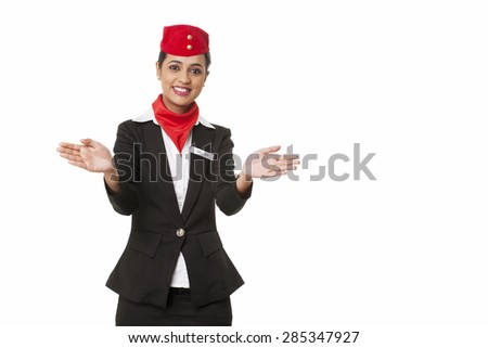 Portrait of young air hostess gesturing over white background - stock photo