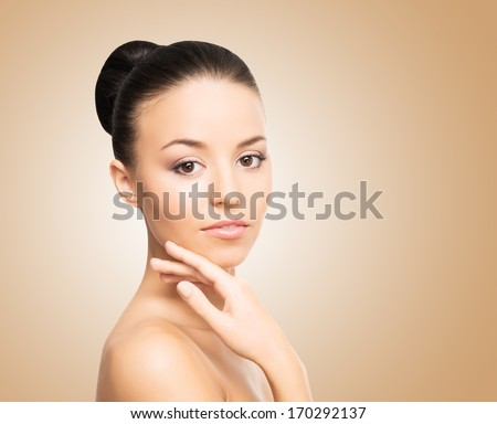 Portrait of young and beautiful girl over brown background - stock photo