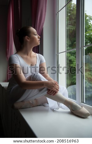 Portrait of young and beautiful modern style ballet dancer sitting on windowsill, looking dreamily outside - stock photo