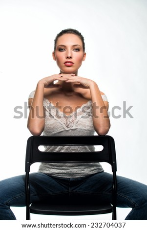 Portrait of young and beautiful woman in 20s seating on chair with hands under her chin. Isolated against white. - stock photo