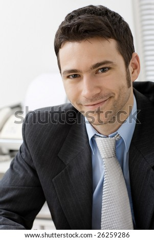 Portrait of young and happy businessman at office desk, smiling. - stock photo