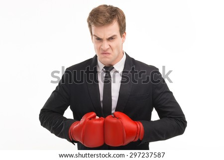 Portrait of young angry businessman wearing suit and red boxing gloves. Isolated on white background - stock photo