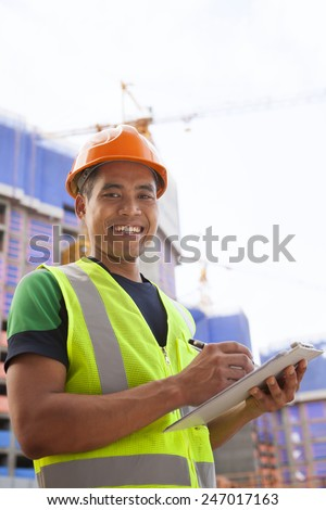 Portrait of young architect holding clipboard against building - stock photo