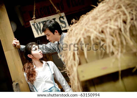 Portrait of young artistic couple in romantic emotion standing beside thatch - stock photo