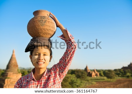 Portrait of Young Asian Burmese traditional female farmer carrying clay pot on head, Bagan, Myanmar - stock photo