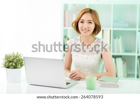 Portrait of young Asian business lady at her workplace - stock photo