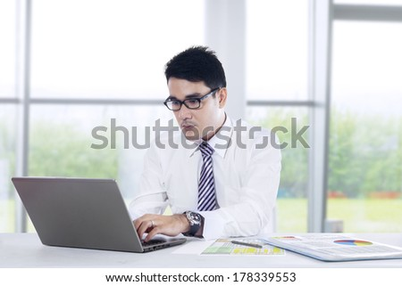 Portrait of young asian businessman typing on laptop computer. - stock photo