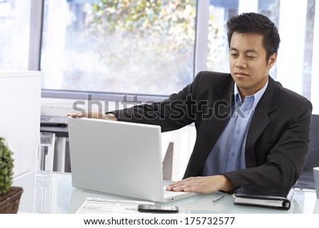 Portrait of young Asian businessman working with laptop in bright office. - stock photo