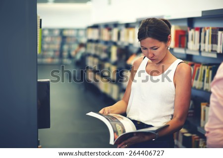 Portrait of young asian female holding open magazine or book while standing near bookshelves, attractive chinese student girl read book in university library, female freelancer in co-working space - stock photo