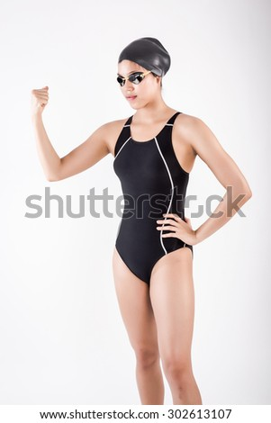 portrait of young  asian female swimmer in blue swimsuit with goggle and swimming hat. strong posing in studio set white background - stock photo