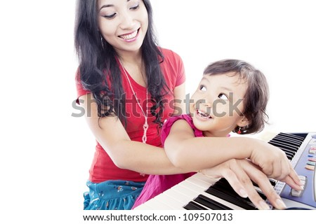 Portrait of young asian mother with her daughter pressing a button on the piano - stock photo