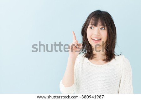 portrait of young asian woman isolated on blue background - stock photo