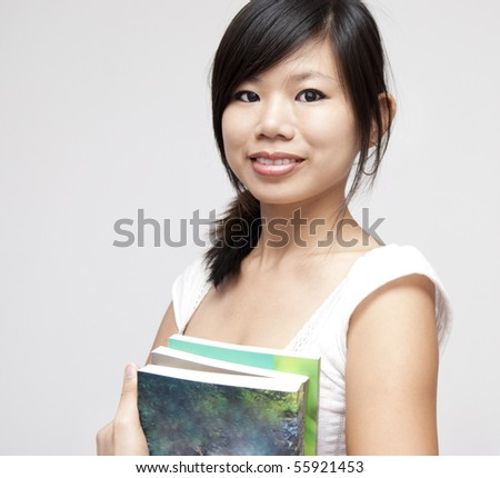 Portrait of young Asian woman with books - stock photo