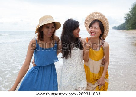 portrait of young asian woman with happiness emotion wearing beautiful dress walking on sea beach and laughing joyful use for people relaxing vacation on destination - stock photo