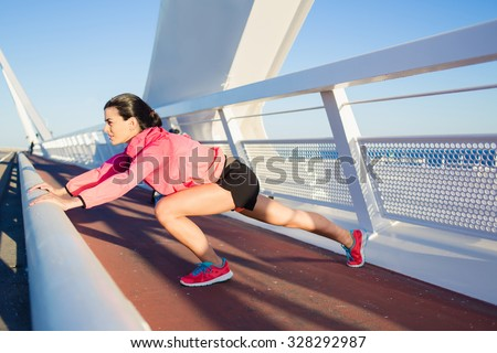 Portrait of young athletic female with a beautiful slender figure stretching muscles before began her evening run in the fresh air, fit woman with perfect body working outdoors during recreation time  - stock photo