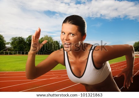 Portrait of young athletic woman running on track - stock photo
