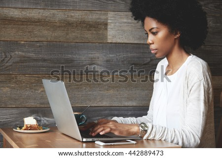 Portrait of young attractive African female blogger, typing a new challenging post during lunchtime at a cafe, with laptop and smart phone with copy space for your promotional content on the table - stock photo